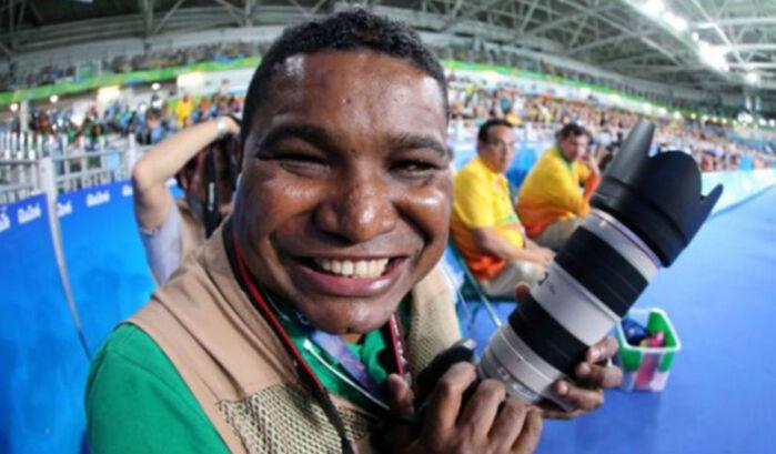 Imagem de João Maia trabalhando em estádio no Rio2016  sentado de costas para um painel azul sorrindo e segurando a câmera profissional com uma lente fixa de 300 mm da série branca da Canon . João usa camiseta verde e colete de imprensa marrom.