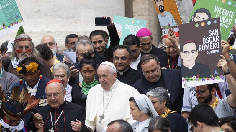 Padre Adelson Araújo atrás do Papa Francisco numa ação com populações indígenas presentes no Sínodo sobre