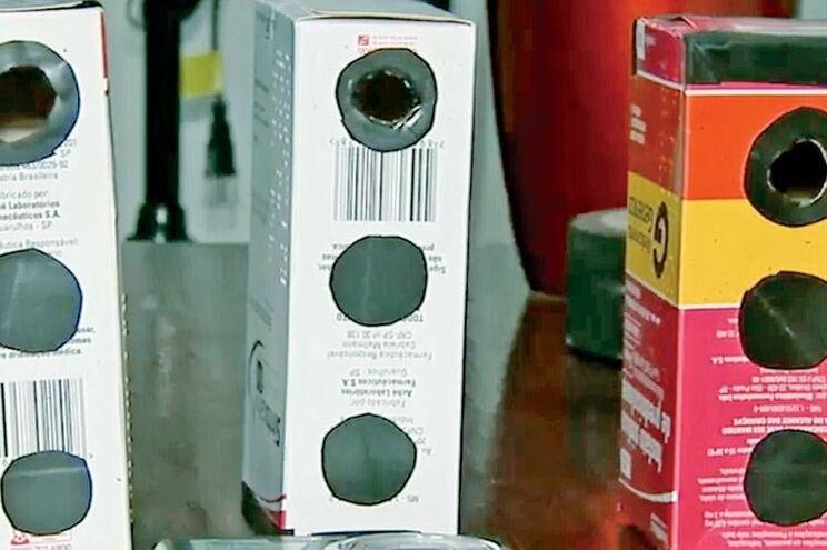 Caixas de remédios com buracos que o professor usava para filmar as alunas
