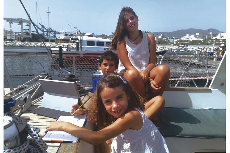 Os irmãos Gonçalves estudam a bordo do veleiro em que viajam
