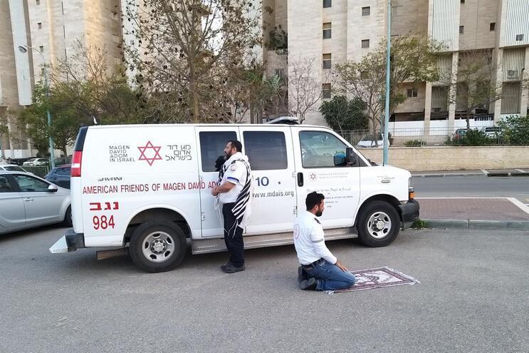 Os paramédicos Avraham Mintz, virado para Jerusalém, e Zoher Abu Jama, ajoelhado na direção de Meca