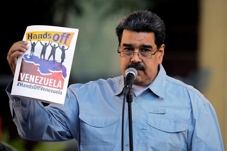 """Maduro segura um cartaz com a frase """"Tirem as mãos da Venezuela"""""""