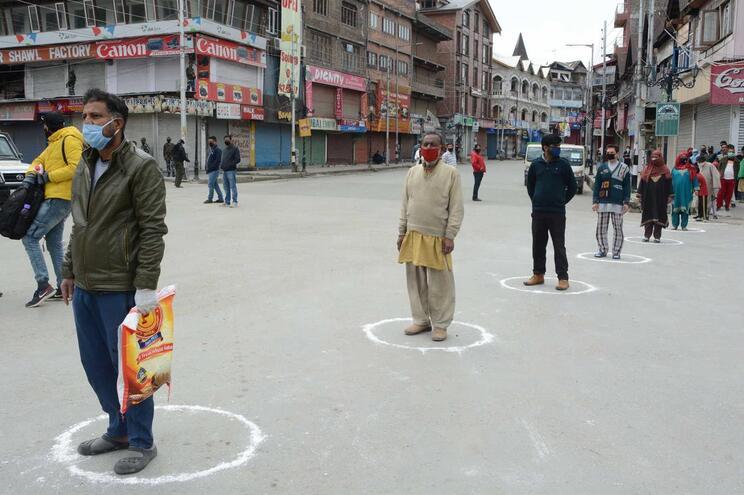 A distância social delimitada rigorosamene na província de Caxemira, enquanto é distribuída comida à