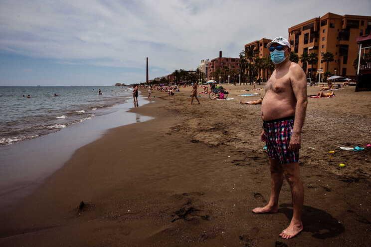 Homem usa máscara em praia de Málaga, em Espanha