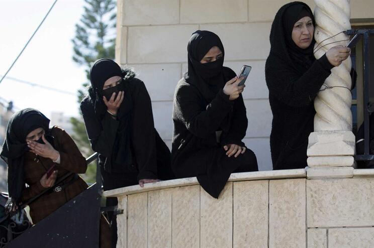 Mulheres palestinianas tiram fotos durante o funeral de um dos jovens mortos em Jenin