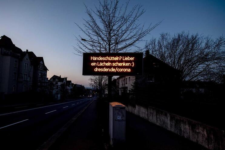 """""""Apertar as mãos? Mais vale dar um sorriso"""", lê-se em Dresden, Alemanha"""