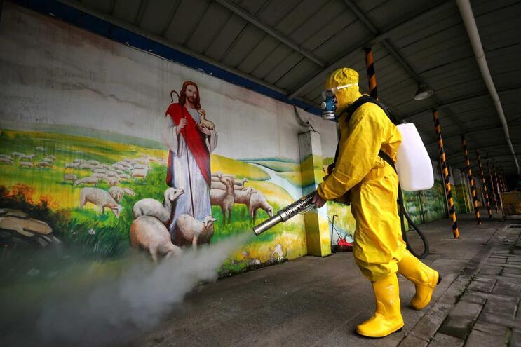 Voluntário desinfecta igreja católica em Wuhan