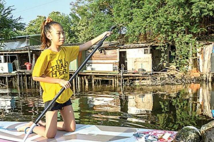 Menina recolhe lixo de Banguecoque em prancha de paddle
