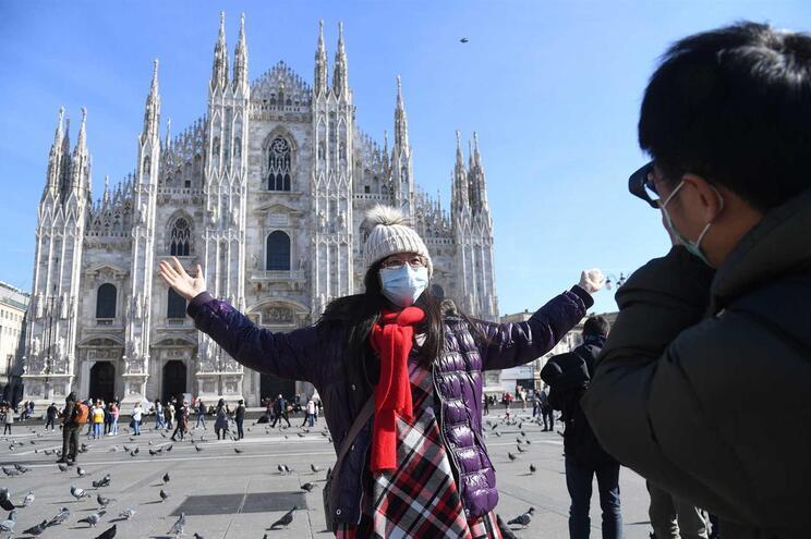 Turistas com máscaras em frente à catedral de Milão, Itália