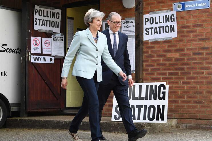 Theresa May acompanhada pelo marido à saída de uma mesa de voto apra as eleições europeias