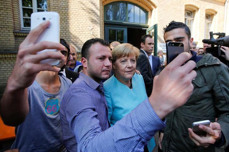 Merkel com um grupo de refugiados