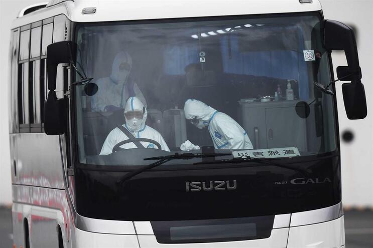 Motorista de autocarro com equipamento de proteção para ir buscar passageiros idosos a sair do navio