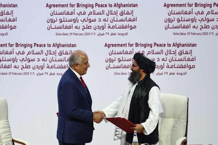 Diplomata afegão-americano Zalmay Khalilzad e Abdul Ghani Baradar durante a assinatura do acordo de paz