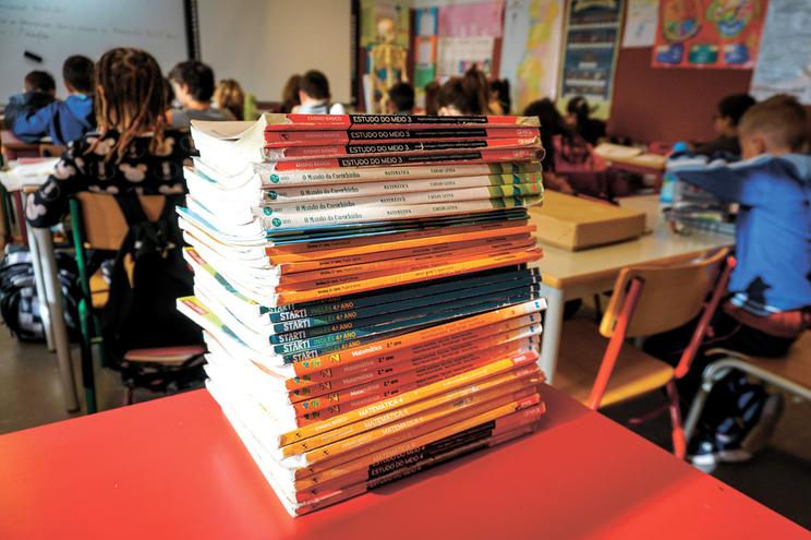 Alunos recebem livros corrigidos a caneta e pintados