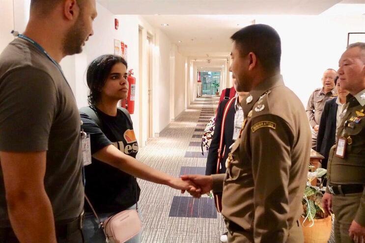 Rahaf Mohammed Al Qunun com autoridades tailandesas, na chegada a um hotel do país