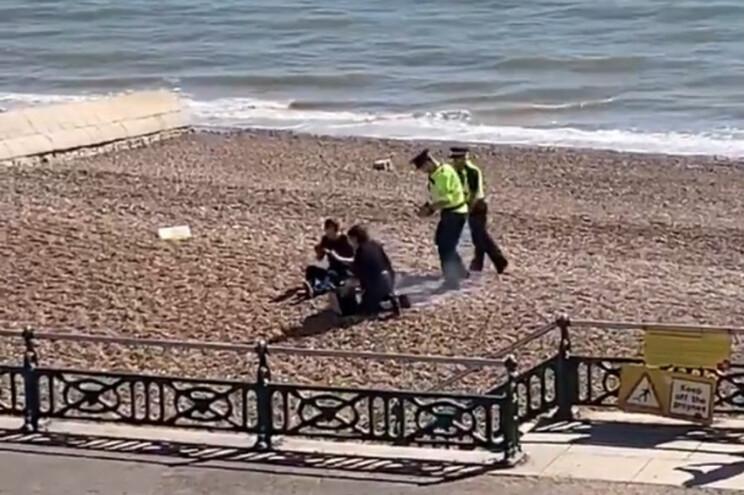 Agentes da polícia labnçam água sobre grelhador onde casal preparava churrasco
