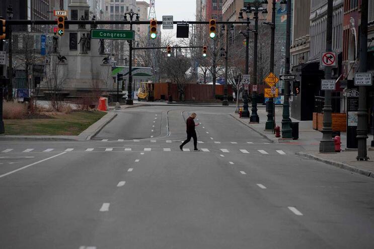 Homem atravessa rua deserta em Detroit