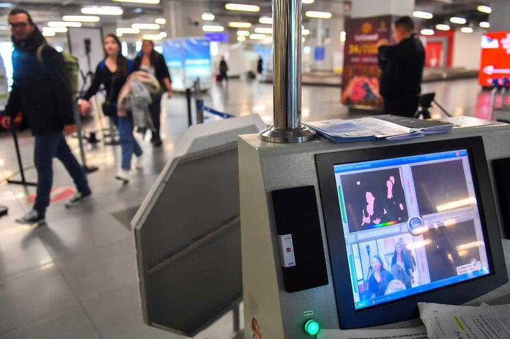 Passageiros passam em frente a uma câmara térmica, instalada no aeropoto de Skopje, na República da Macedónia