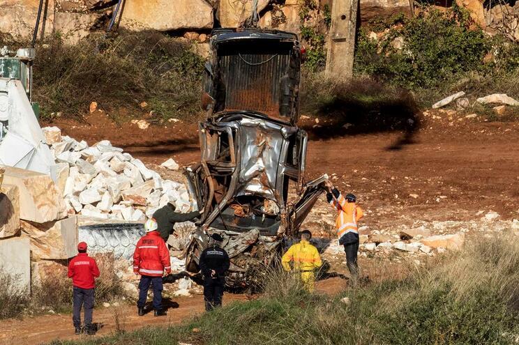 Elementos da Proteção Civil e dos bombeiros retiram uma viatura que estava submersa no fundo da pedreira