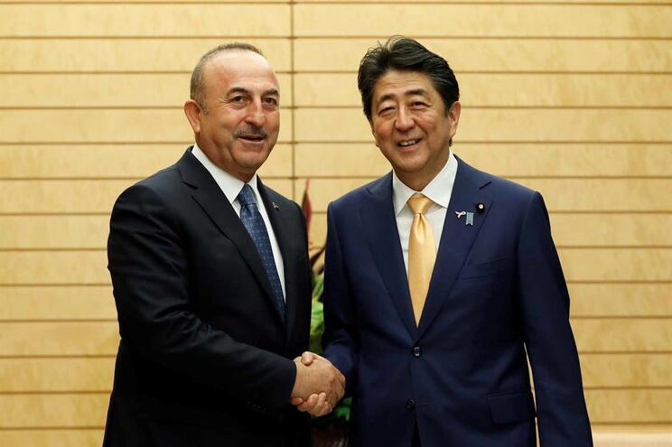 Oministro turco dos Negócios Estrangeiros, Mevlut Cavusoglu (E), cumprimenta o primeiro-ministro japonês