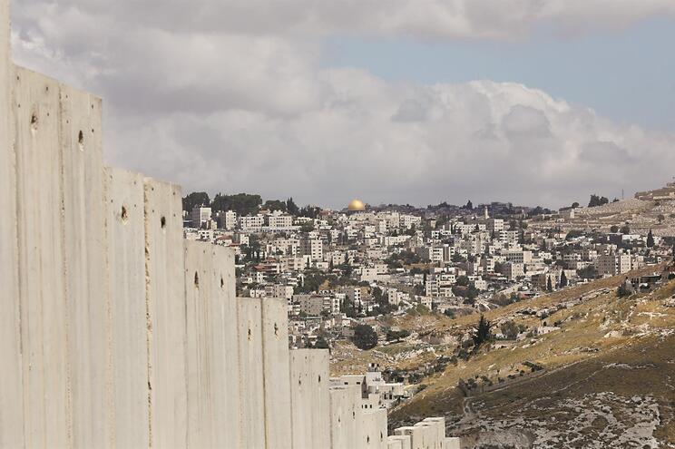 O muro que delimita territórios ocupados, com a Cidade Velha de Jerusalém ao fundo