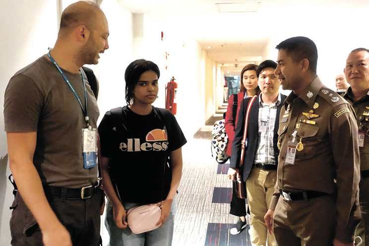 Rahaf com um elemento do ACNUR e o responsável da Polícia de Imigração tailandesa, Surachate Hakparn