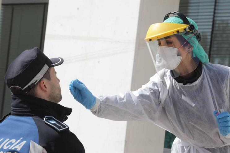 Agente da polícia faz exame para testar a existência do novo coronavírus, em Madrid