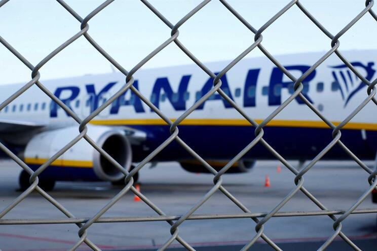 FILE PHOTO: An aircraft of low-cost airliner Ryanair is seen behind a fence while being parked at the