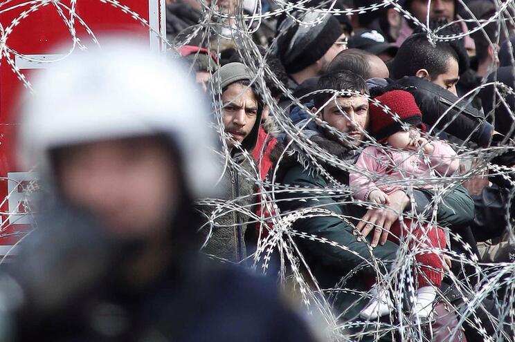 Migrantes e refugiados no lado turco da passagem fechada da fronteira com Kastanies, entre a Grécia e