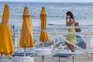 Mulher usa máscara em praia de Palermo, na Itália