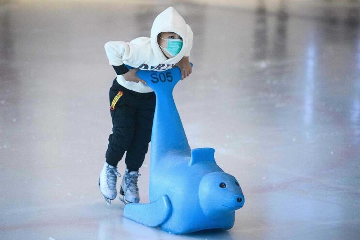 Criança brinca no gelo durante o feriado do Novo Ano Lunar chinês