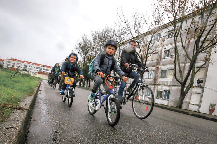 Crianças entre os 3 e os 8 anos vão de bicicleta para a escola, acompanhadas pelos pais, em Aveiro