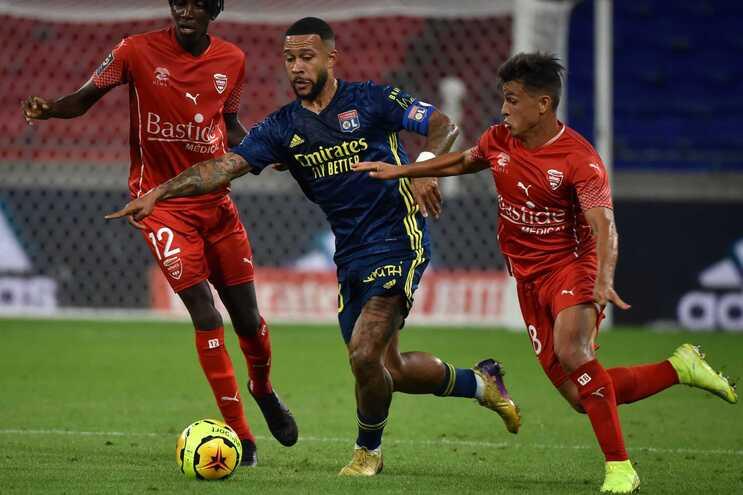 Rafael Pereira da Silva, do Lyon, tenta fugir a dois adversários do Nimes