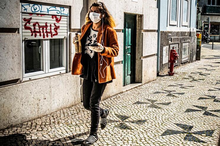 Mulher usa máscara em rua de Lisboa