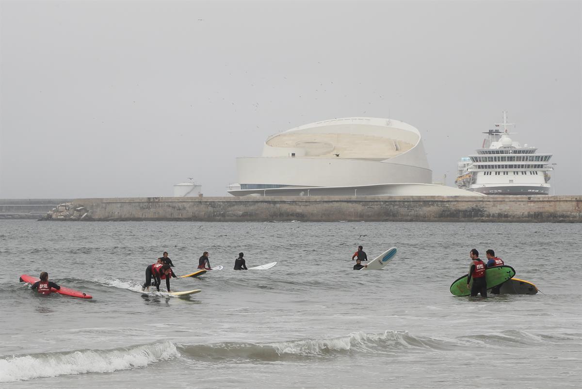 Surf em Matosinhos, com o terminal de Leixões ao fundo