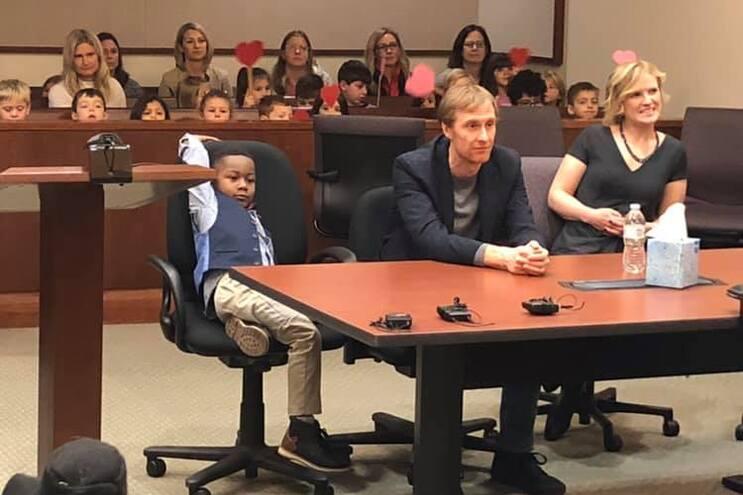 O menino, identificado como Michael, foi aplaudido pelos colegas quando foi formalmente adotado