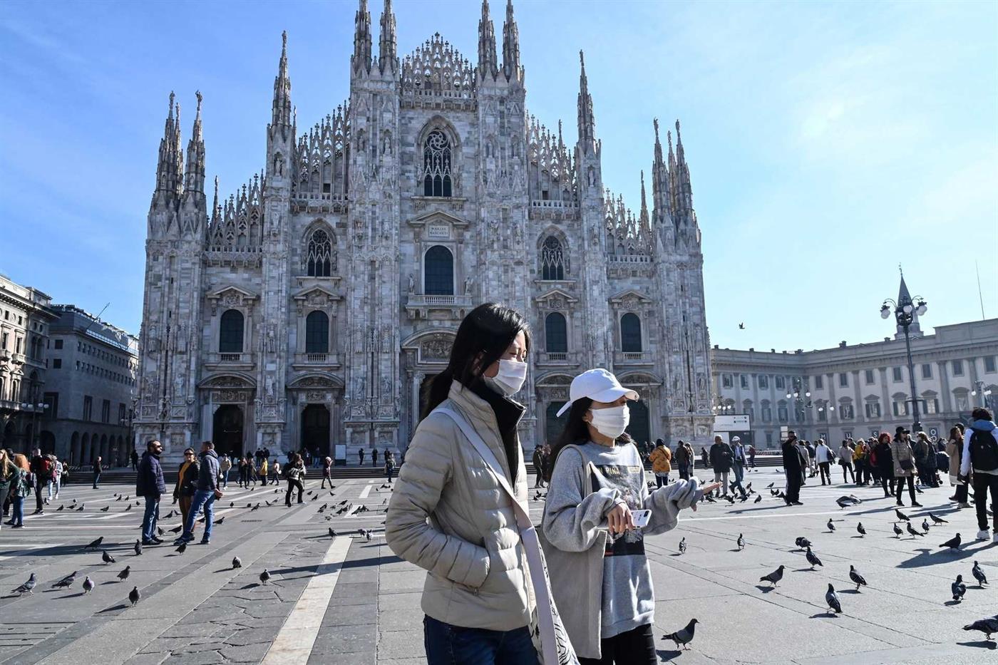 Turistas passeiam de máscara em Milão, uma das cidades na região mais fetada de Itália
