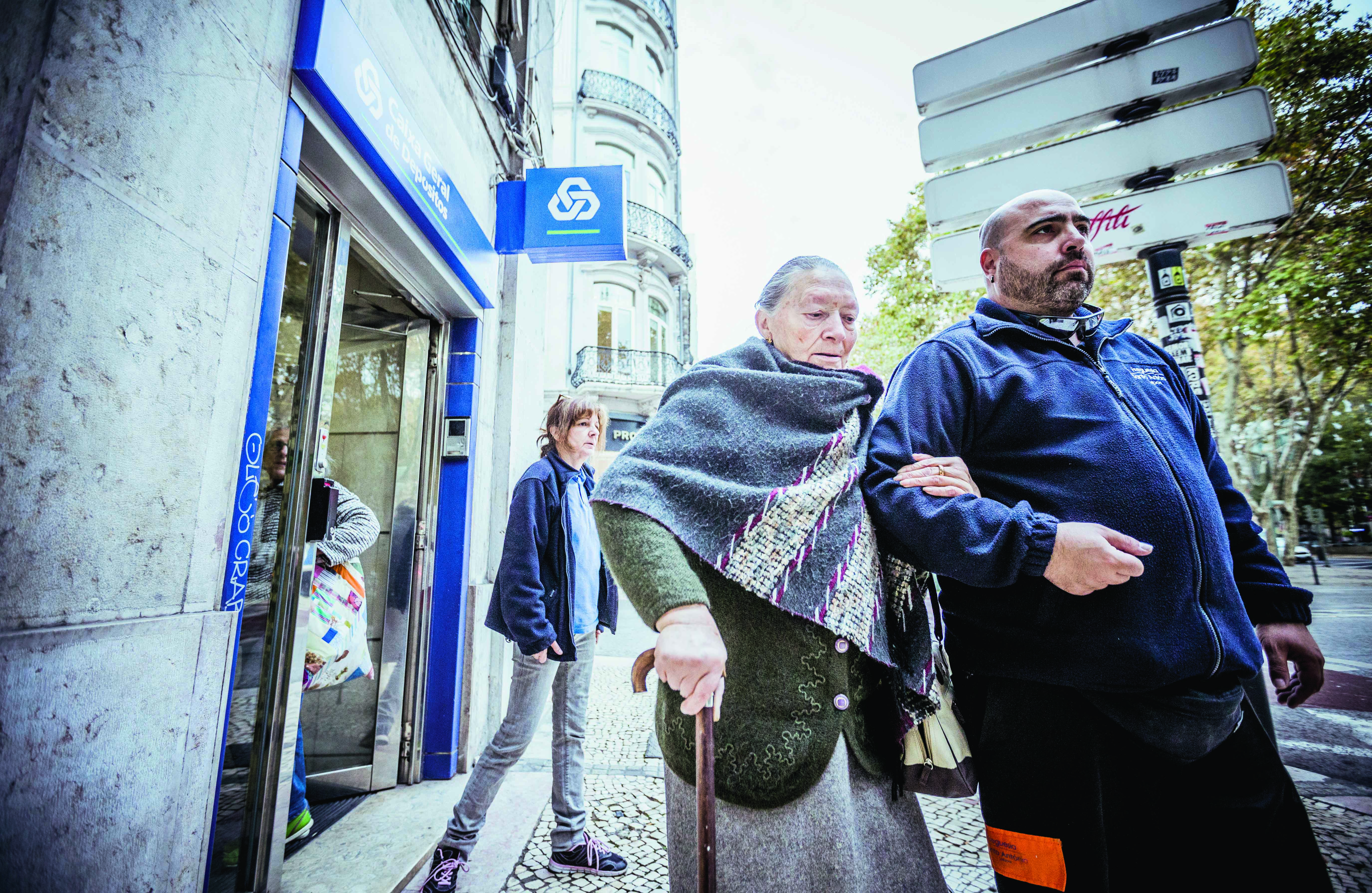 O Sr. Reis e uma técnica  ajudam Odete Peres, utente do programa Vassouras & Companhia, a ir à sua agência