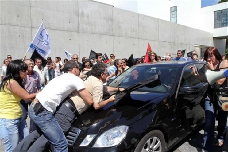 Agente de segurança detém um manifestante que se deita no carro do ministro