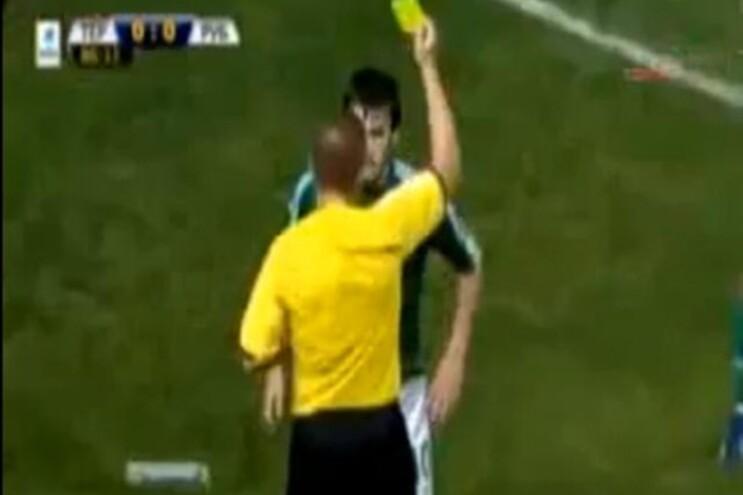 O árbitro Mikhail Vilkov mostra cartão amarelo ao capitão da equipa da casa