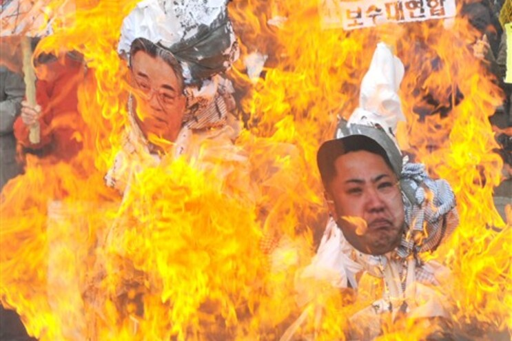 Ativistas sul-coreanos queimam cartazes com imagens do antigo (Kim Il-Sung) e atual líder (Kim Jong-Un)