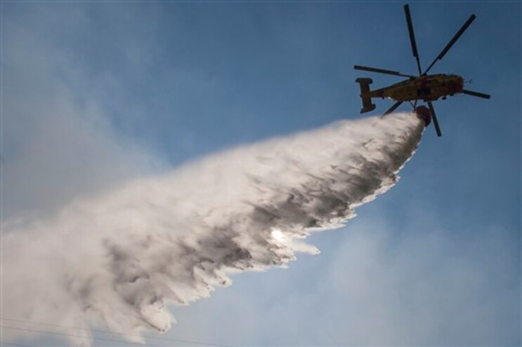 Descarga de água por um helicóptero que combate fogos