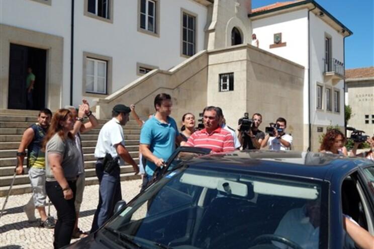 Suspeito, a entrar para o carro, de camisola vermelha, saiu do tribunal sob o protesto de dezenas de