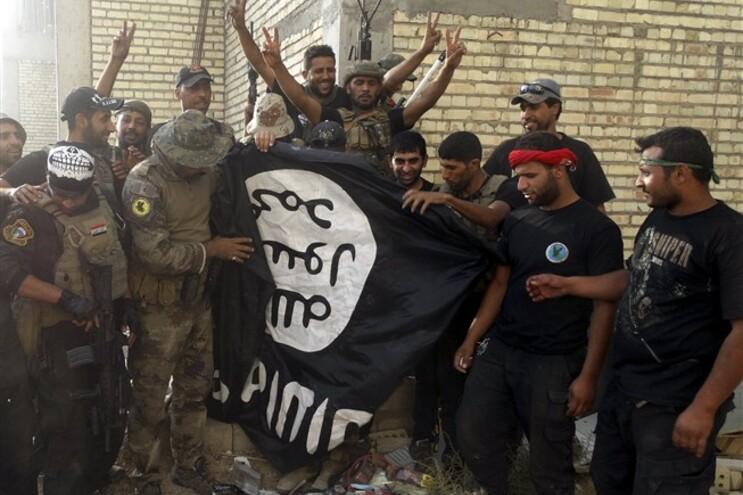 Elementos das forças de combate iraquianas com a bandeira do Estado Islâmico
