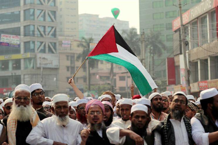 Manifestantes com a bandeira da Palestina em protesto contra  decisão de mudar a embaixada dos EUA para