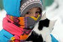 epa05644030 A little girl caries a cat while wrapped up against the cold in Bishkek Kyrgyzstan 23 November