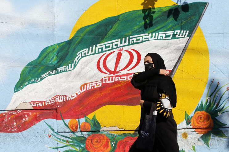 Mulher passa em frente a mural com a bandeira do Irão, em Teerão
