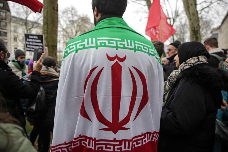 Homem com a bandeira do Irão durante uma manifestação em Bruxelas, na Bélgica