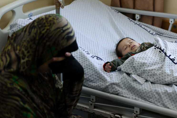 Mulher palestiniana com o filho bebé num hospital em Khan Yunis, no sul da Faixa de Gaza