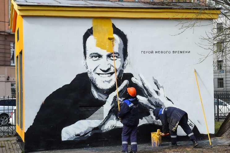 """Trabalhadores cobrem grafito de Navalny com a inscrição """"O herói dos novos tempos"""", em São Petersburgo"""
